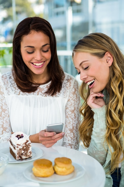 Two girls watch a phone while eating Premium Photo