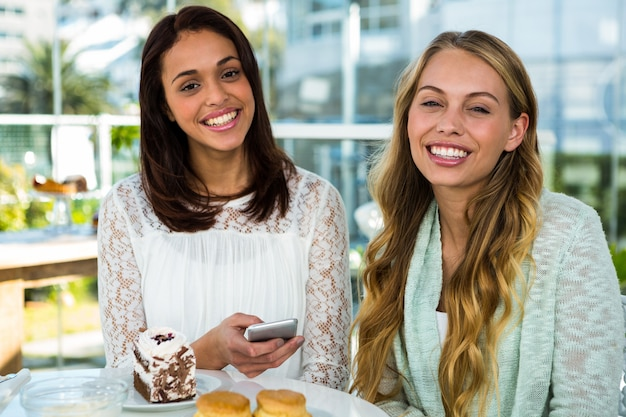 Two girls watch use phone while eating Premium Photo