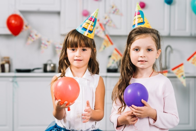 Two girls with red and purple balloons standing in kitchen Free Photo