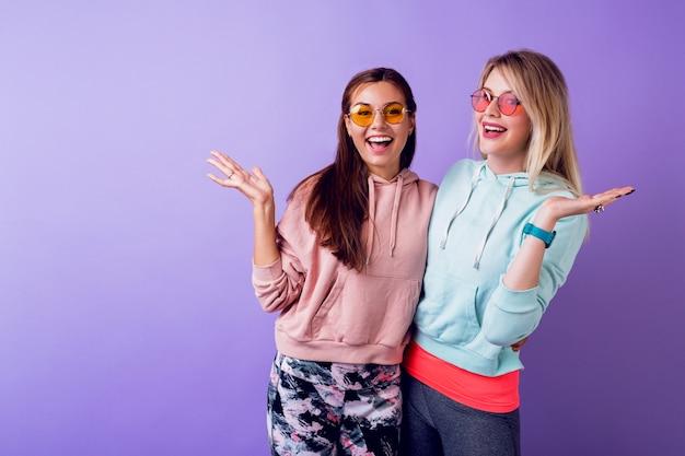 驚きの顔で二人の女の子が紫色の壁の上にとどまっています。おしゃれなパーカーとかっこいいメガネを着ています。 無料写真