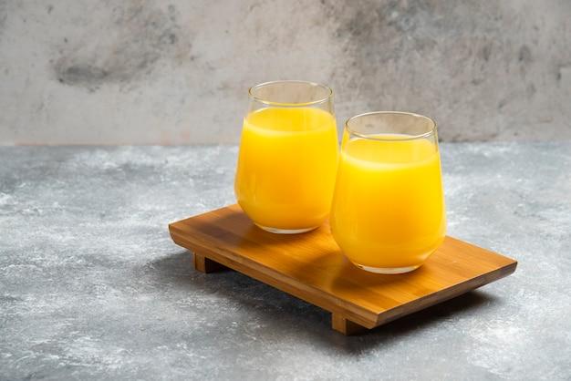 木の板に新鮮なオレンジジュースの2つのガラスカップ。 無料写真