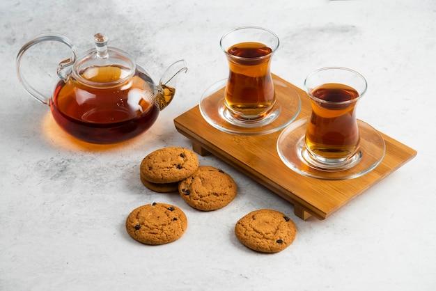 おいしいクッキーとお茶の2つのガラスカップ。 無料写真