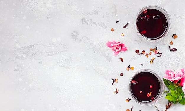 ピンクの花と乾燥茶葉と赤いホットハイビスカスティーの2つのガラスのコップ。トップビュー、コピースペース。 Premium写真