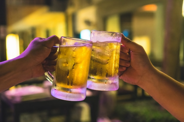 Two glasses of beer cheers together between friend in the low light bar and restaurant Premium Photo