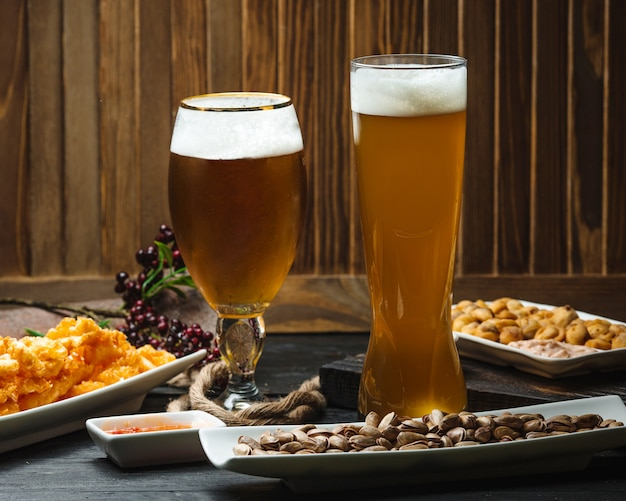 Two glasses of beer served with pistachios, nuggets and sweet chili sauce Free Photo
