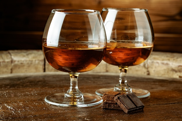 Two glasses of bourbon or scotch, or brandy and pieces of dark chocolate Premium Photo