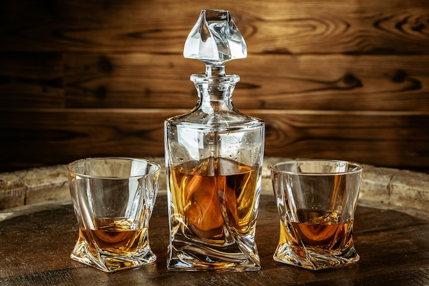 Two glasses of brandy or cognac and bottle on wooden table Premium Photo