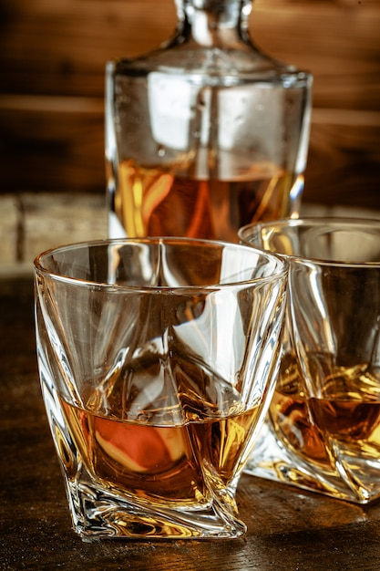 Two glasses of brandy or cognac and bottle on the wooden table Premium Photo