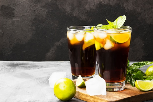 Two glasses of cocktail cuba libre on a dark background. copy space. food background Premium Photo