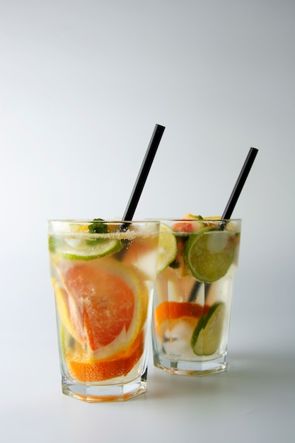 Two glasses of cold summer homemade cocktail with lemon, lime, orange and grapefruit. Premium Photo