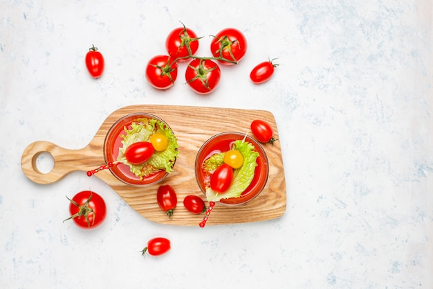 Two glasses of fresh tomato juice and tomatoes on gray concrete surface Free Photo