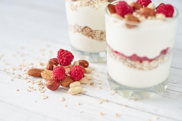 Two glasses of greek yogurt granola with raspberries, oatmeal flakes and nuts Premium Photo