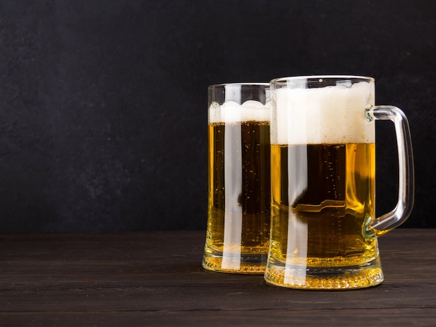 Two glasses of lager served on old wooden planks Premium Photo