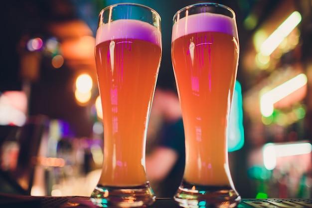 バーテーブルのビール2杯。ビールの背景をタップします。 Premium写真