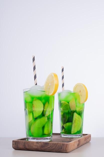 白い壁にフルーツスライスと新鮮な果物のジュース2杯。 無料写真