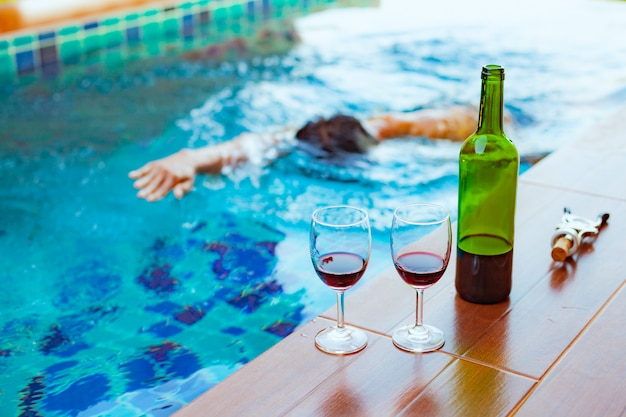 Two glasses of red wine near the swimming pool with a man is swimming in the pool Premium Photo