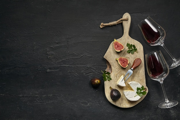 Two glasses of red wine and a tasty cheese plate with fruit on a wooden kitchen plate on the black stone Free Photo
