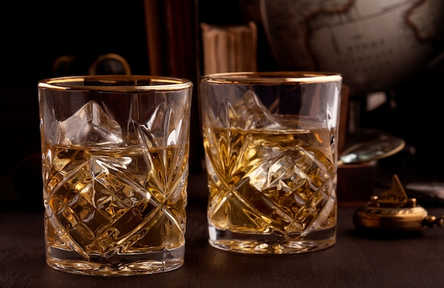 Two glasses of whiskey in the library Premium Photo