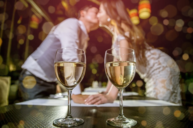 Two glasses of wine place on table. there are asian couple kissing together on blured background. Premium Photo