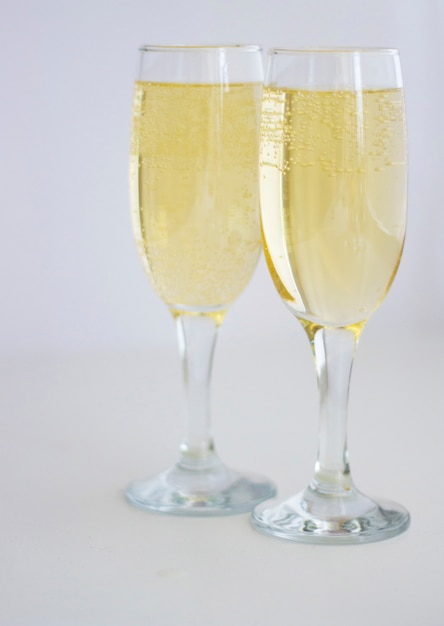 Two glasses with champagne on a white background. Premium Photo
