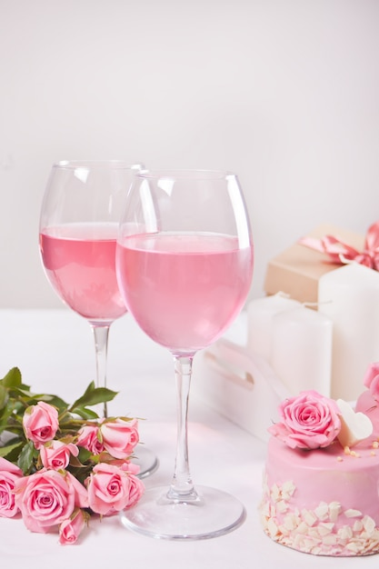 Two glasses with pink grape wine with rose flowers. romantic dinner concept. Premium Photo
