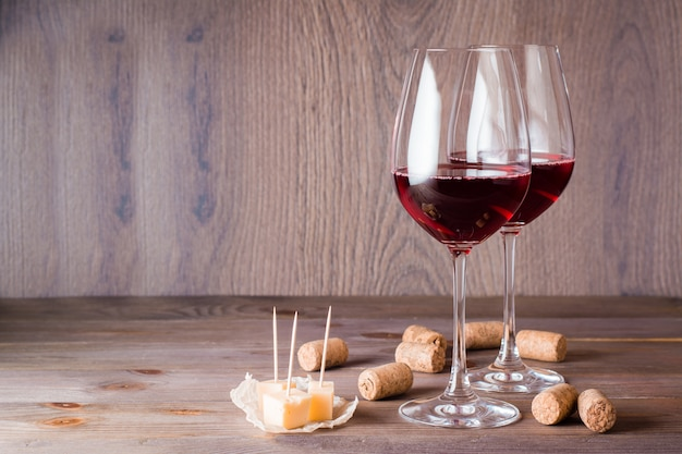 Two glasses with red wine, pieces of cheese and cork on a wooden table Premium Photo
