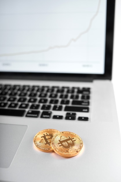 Two golden bitcoins as main cryptocurrencies placed on silver laptop with blurred chart on screen on background. Premium Photo