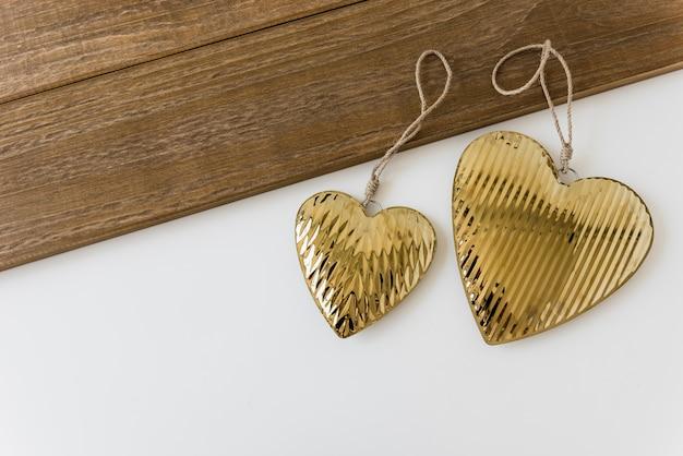 Two golden heart shape on white backdrop Free Photo