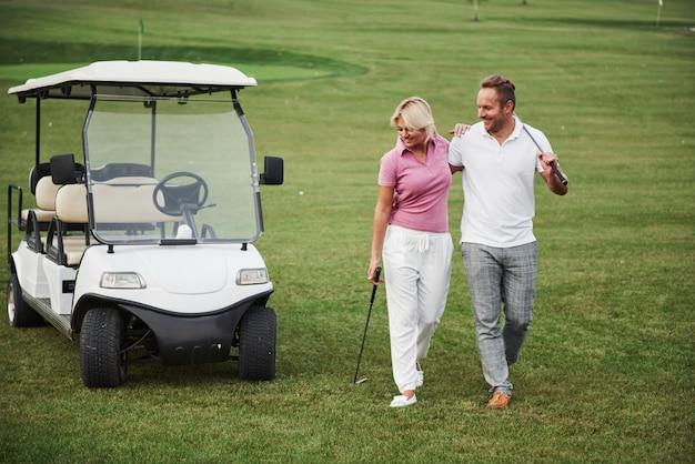 두 명의 골퍼, 여자와 남자가 다음 홀로갑니다. 학생은 개인 트레이너와 함께 가서 스포츠에서 성공한 것에 만족합니다. 프리미엄 사진