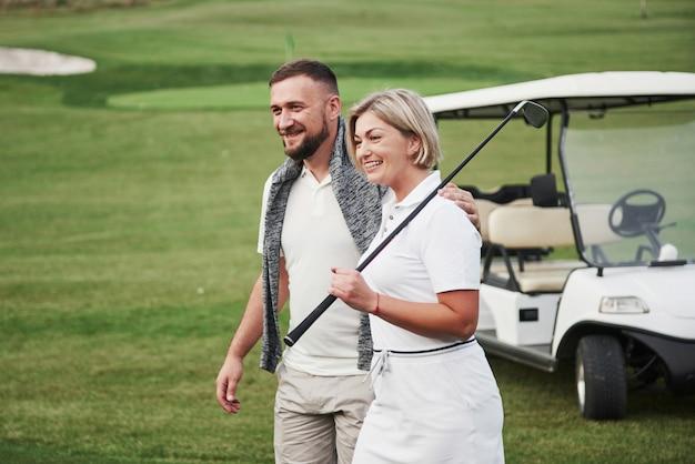 여자와 남자의 두 골퍼가 다음 홀로갑니다. 학생은 개인 트레이너와 함께 가서 스포츠에서 성공한 것에 만족합니다. 프리미엄 사진