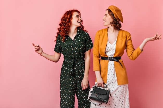 お互いを見つめている2人の気さくな女性。ピンクの背景で話している洗練された女の子のスタジオショット。 無料写真