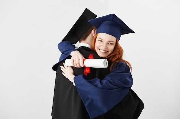 白い表面を受け入れる2つの卒業生 無料写真