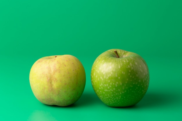 Two green apples on a green vertical Premium Photo