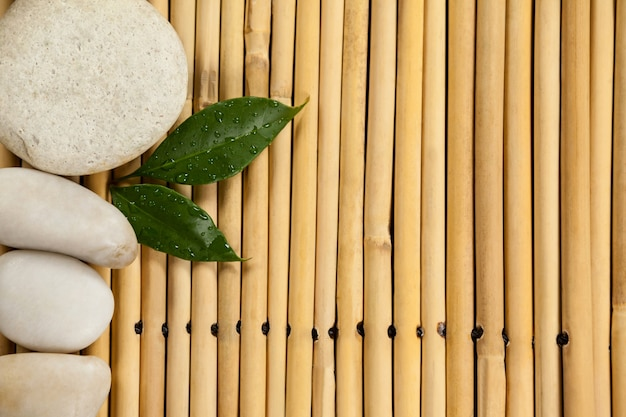 Two green leaves and four white stones on the bamboo mat Free Photo