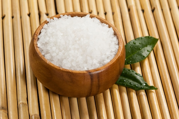 Two green leaves and sea salt in wooden bowl Free Photo