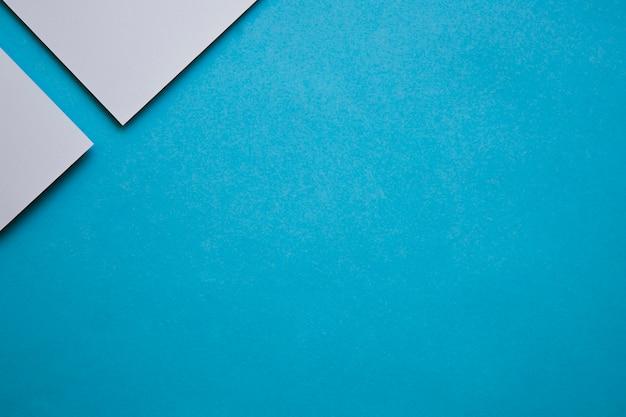 Due carte di cartone grigio all'angolo dello sfondo blu Foto Gratuite