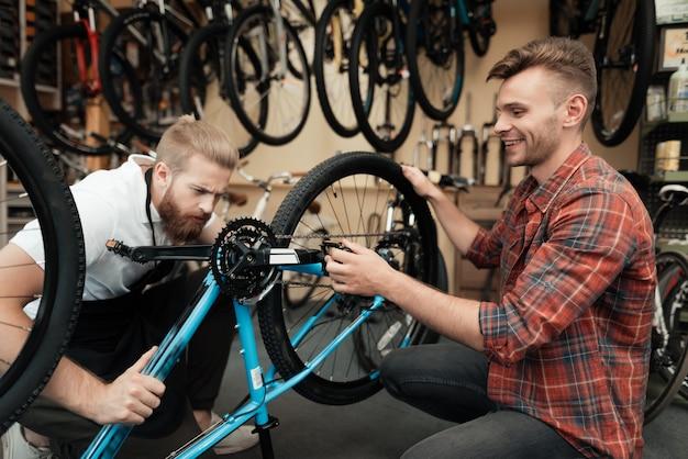 Two guys examine bicycle in sport workshop Premium Photo