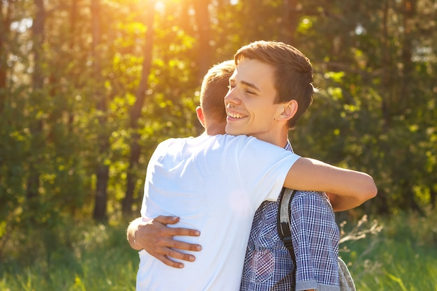 Premium Photo   Two guys hugging on a sunny day