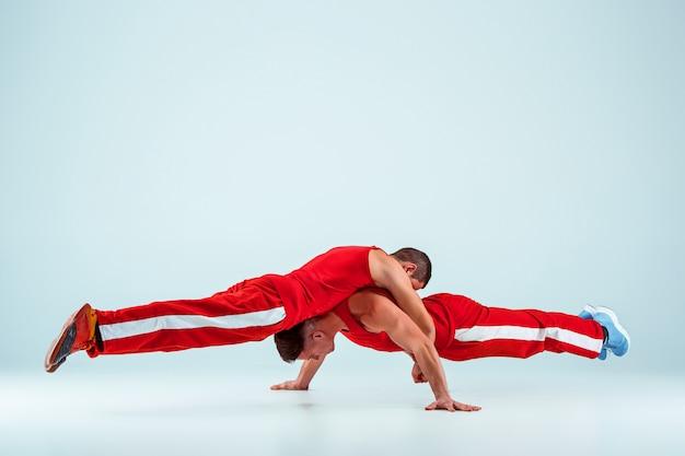 Due uomini caucasici acrobatici relativi alla ginnastica sulla posa dell'equilibrio Foto Gratuite