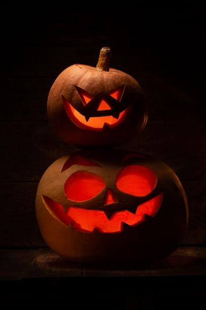Две тыквы на хэллоуин со страшным лицом в темноте Premium Фотографии