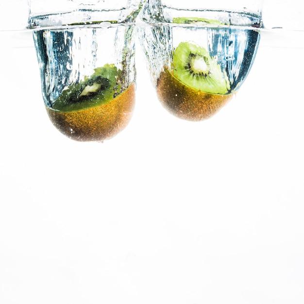 Two halved kiwi splashing in water over the white background Free Photo