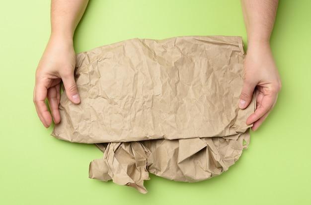 Две руки держит кусок мятой коричневой бумаги изолированы Premium Фотографии