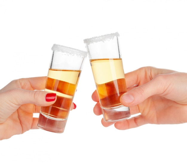 Two hands clinking glasses with shot cocktail isolated on white Premium Photo