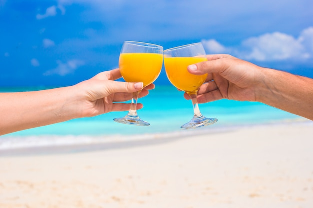 Two hands hold glasses with orange juice in the beach Premium Photo