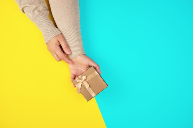Two hands hold a paper closed golden box Premium Photo