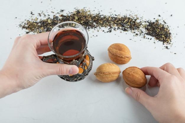 ハーブティーと甘いクルミの形をしたクッキーのカップを持っている両手。 無料写真
