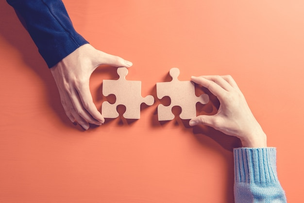 Two hands holding jigsaw, concept for teamwork building a success. Premium Photo