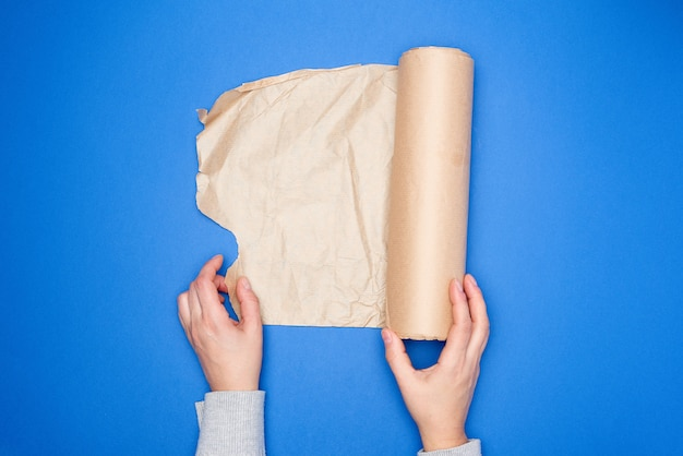 Two hands holding a roll of brown parchment paper on a blue surface Premium Photo
