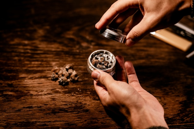 Two hands using a marihuana grinder to shred the buds before rolling a joint. Premium Photo