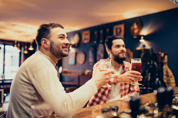 Two handsome bearded man drinking beer in pub Free Photo